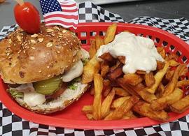 Assiette composée d'un burger, de frites maison et sa sauce, sur une nappe à damier noir et blanc